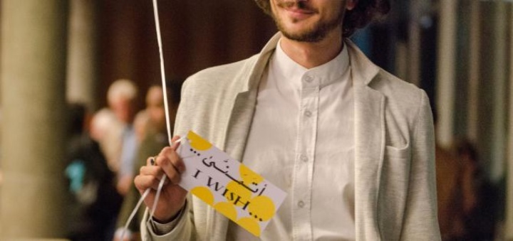 IUSD students holding a card that says 'I wish' in English and Arabic. (c)